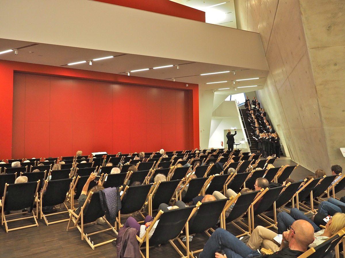 Wandelkonzert. Ob auf der Treppe zum Audimax, auf der Empore oder vor der roten Pforte, der A-Capella-Gesang des Kammerchors St. Michaelis Lüneburg klingt immer gut. Wandelbar müssen an diesem Abend auch die Besucher sein, denn mehr Musik wartet auf sie in weiteren Räumen.