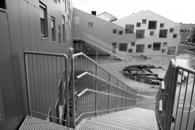 Skovbakkeskolen, Odder. Alle Körper der Schule gruppieren sich um einen zentralen Platz draußen. Drinnen laufen die Wege und Räume ebenfalls auf einen zentralen Platz zu.