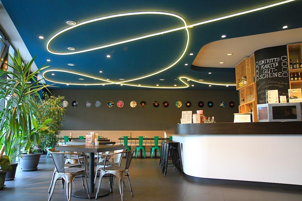 Weltspiegel. Die Kinobar mit dem L-förmigen Tresen und den schwungvollen LED-Linien.