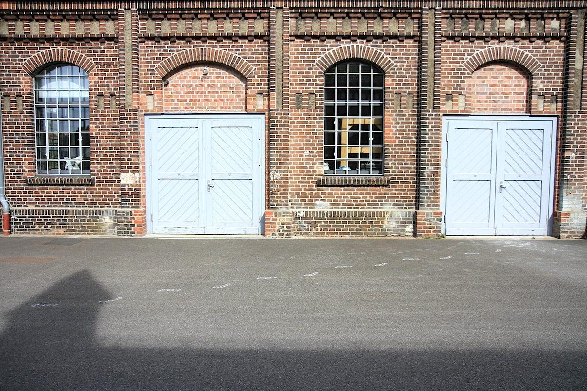 Symmetrie. Beim Rundgang auf die harmonische Zuordnung der Gebäude zueinander und die detaillierte Fassadengestaltung achten.