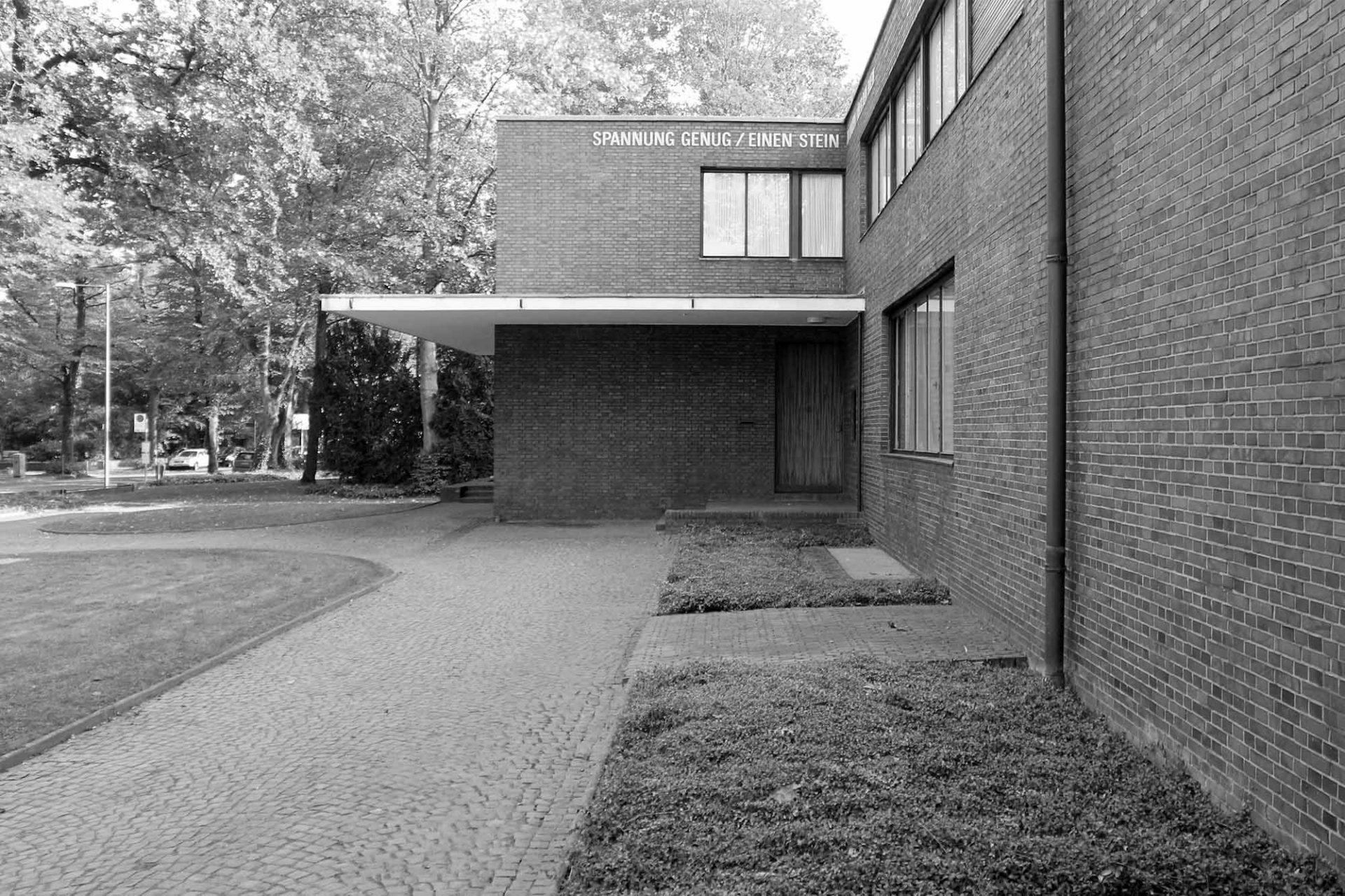 """Haus Esters. 1985 installierte Lawrence Weiner den Schriftzug """"SPANNUNG GENUG / EINEN STEIN ZU HALTEN / ÜBER DEM RHEIN"""" über dem Eingang."""