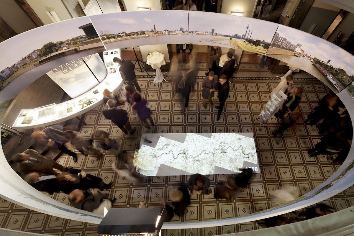 Dynamik und Wandel. Die Entwicklung der Städte am Rhein 1910-2010+.  Passend zum mobilen M:AI-Konzept konnten Besucher das Thema in realer Architektur erleben. Die Ausstellung wurde in Bauwerken gezeigt, die mit dem Thema unmittelbar zusammenhingen.