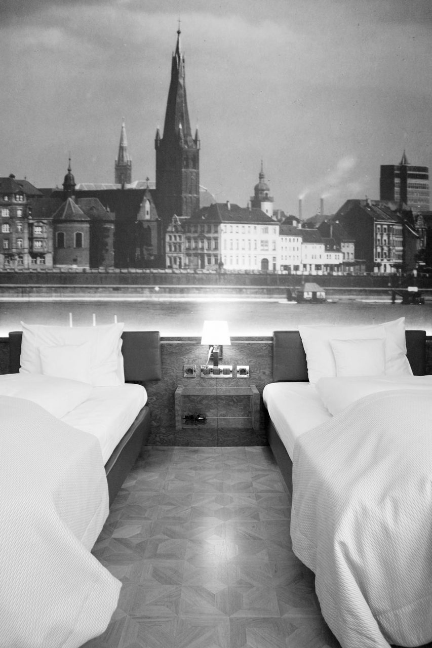Derag Livinghotel De Medici.  Neben europäischer Kunst findet man hier auch lokale Verweise, so wie die Fototapete mit der Düsseldorfer Rheinpromenade.