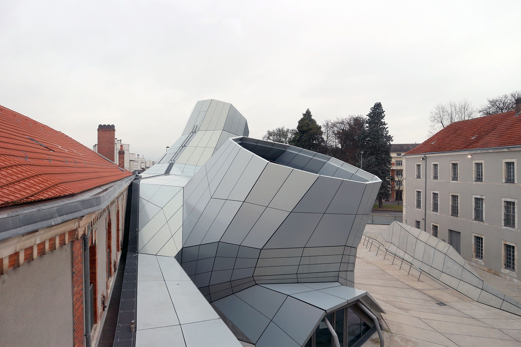 Orléans. Der zeichenhafte Erweiterungsbau setzt einen klaren Kontrast zu den bestehenden Gebäuden eines ehemaligen Militärdepots.