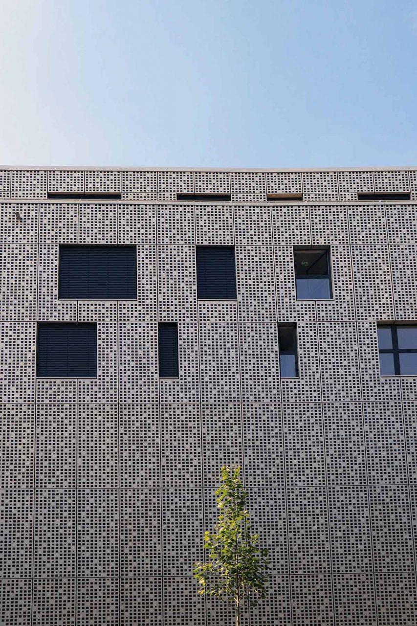Magnus 31. An der verkehrsreichen Magnusstraße (Ecke Alter Wallgasse) grenzt die wertige Fassadenbekleidung aus eloxierten und perforierten Metalltafeln von V-Architekten, schützend nach außen ab.