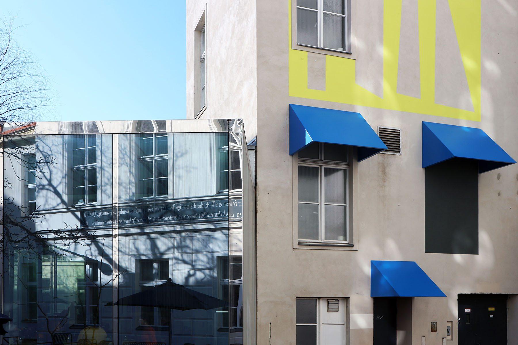 """Stepping stairs. Im Innenhof realisierte Judith Hopf eine Auftragsarbeit, die unverkennbar eine Anspielung an John Hejduks Kreuzberger Gebäudekomplex """"Berlin-Masque"""" darstellt. Die Installation mit langer, roter Zunge und blondem Haar verbleibt dauerhaft an der Fassade des Innenhofs."""