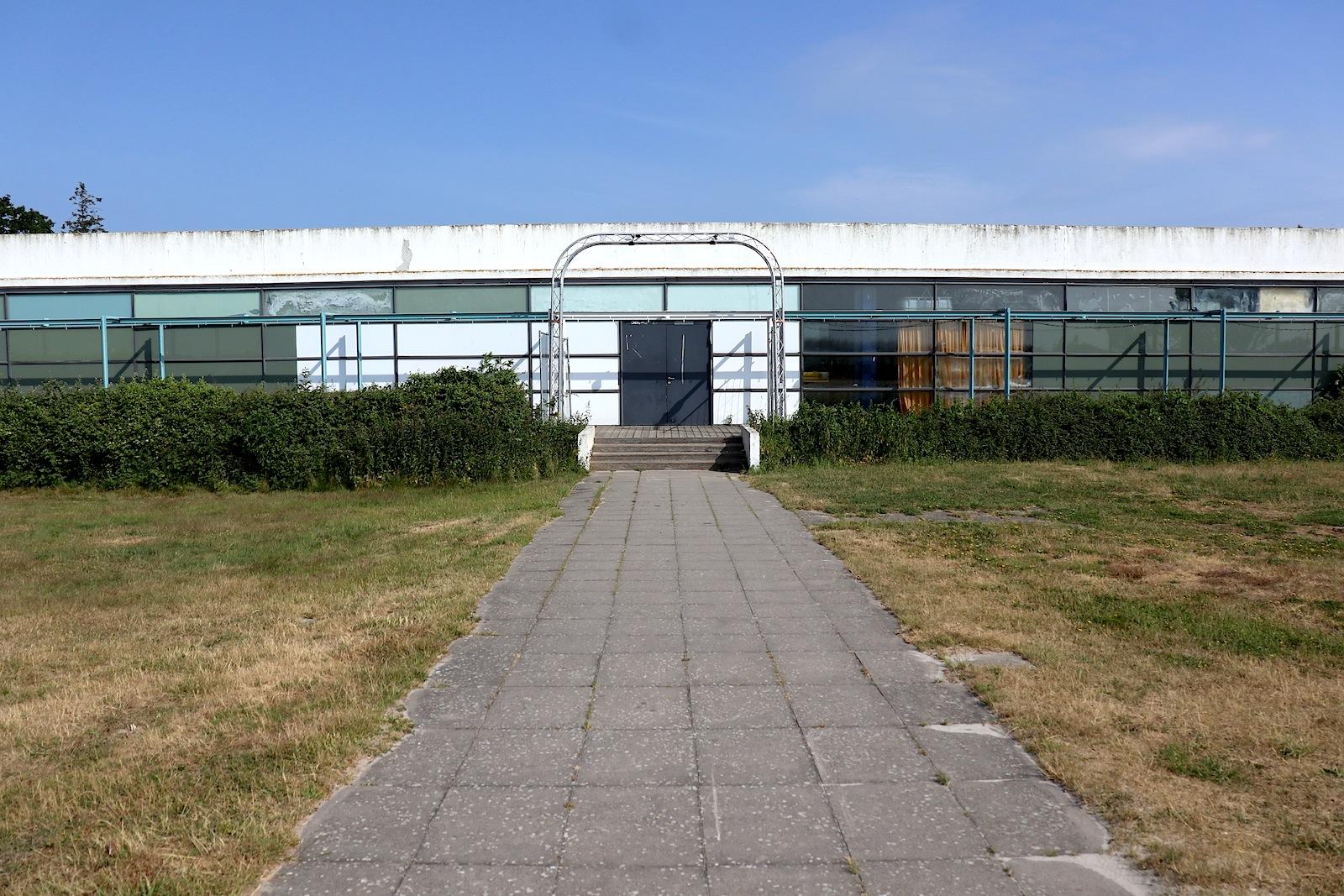 Haus des Gastes. Heute ist der eingeschossige Stahlskelettbau in einem schlechten Zustand und soll nach dem Rückkauf instandgesetzt werden. Vielleicht als Kulturzentrum? Gar als Arne Jacobsen-Museum?