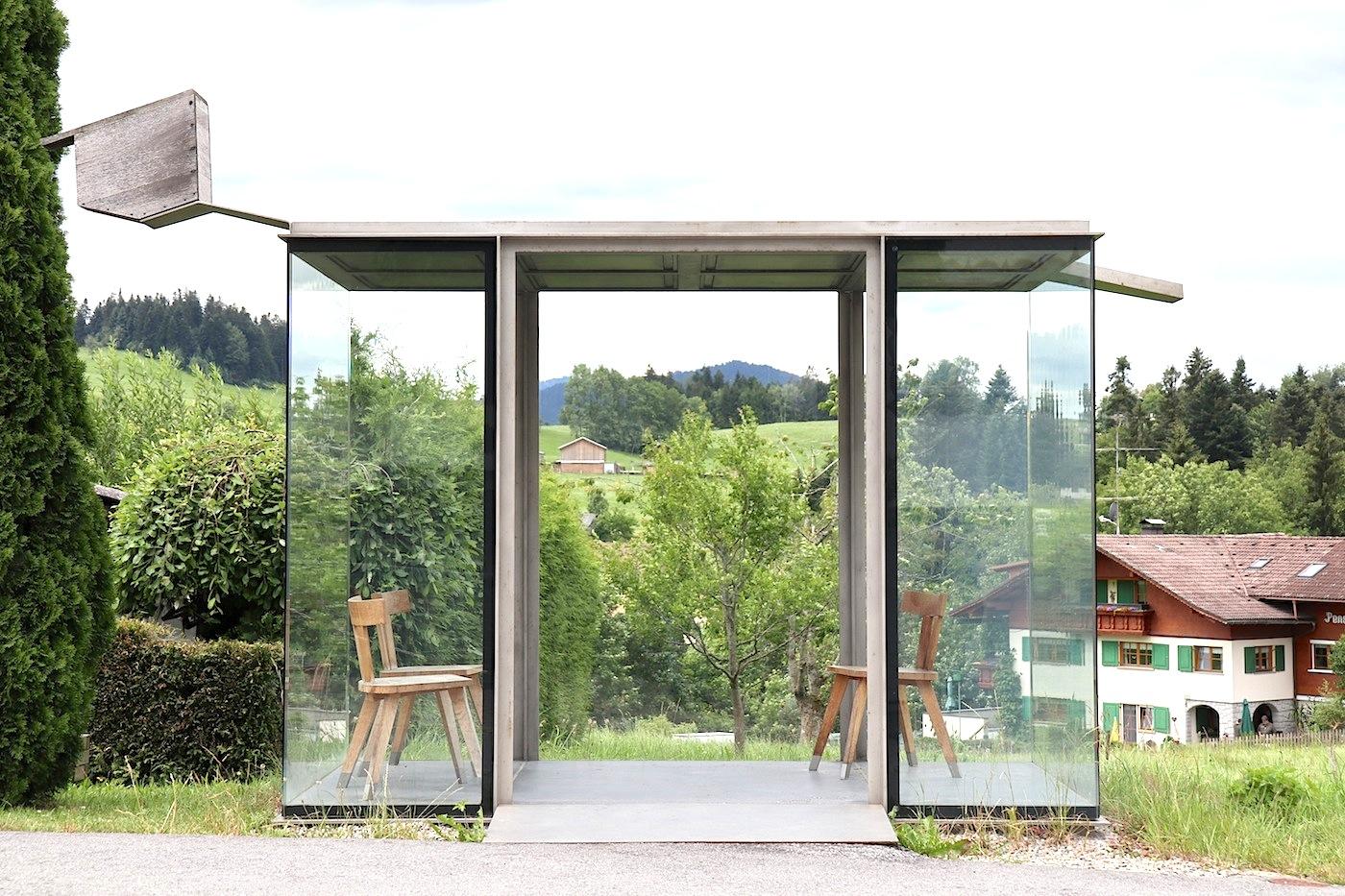 BUS:STOP in Zwing. Das von Smiljan Radic Clarke entworfene Wartehäuschen ist eine Referenz an die Bregenzerwälder Stube. Dazu hat er ein Stück Stube als Glaspavillon mit einer Kassettendecke aus schwarzem Beton in die Landschaft gesetzt. Drei rustikale Holzstühle und ein Vogelhaus komplettieren es.
