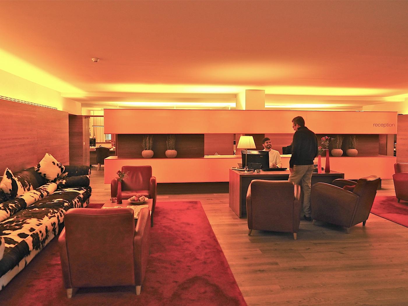 Einstimmung. Die Lobby nimmt einiges aus den Zimmern vorweg: die Muster des Lärchenholzes am Boden und den Wänden, das Spiel des indirekten Lichts, das Rot der Sessel und Teppiche. Nur die Sofas in Kuhfell schwarz-weiß setzen einen eigenen Akzent.