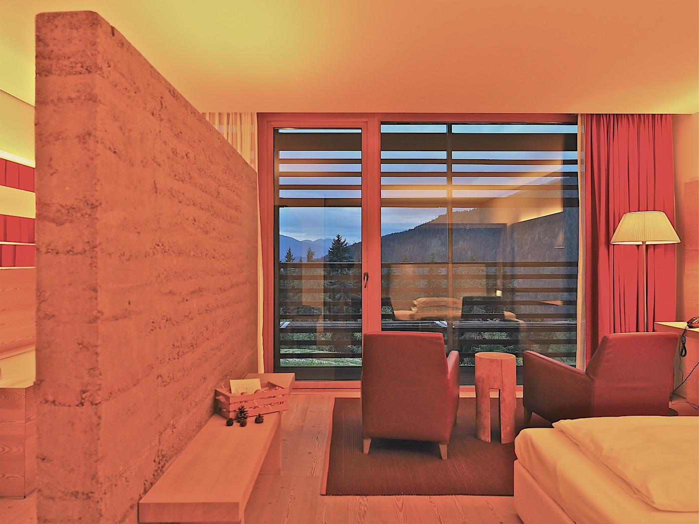 Sinnlichkeit. Auf den 36 Quadratmetern der Standardzimmer spricht vor allem das Holz der Lärche die Sinne an: gröber gemustert mit Astlöchern die geschliffenen Böden, fein gemasert die Verkleidungen und mit Sandstrahl geriffelt die Türen. Die Lehmwand, die das Bad abteilt, hilft das Raumklima natürlich zu regulieren und gibt bei Bedarf Strahlungswärme ab.