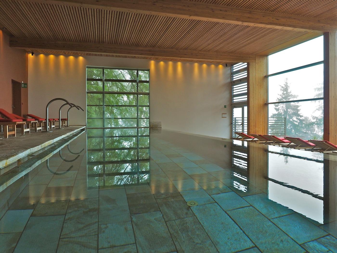 Infinity. Die Schwimmhalle mit ihren Böden aus Silberquarzit öffnet sich zu einem Whirlpool im Freien und einer Terrasse im Süden.