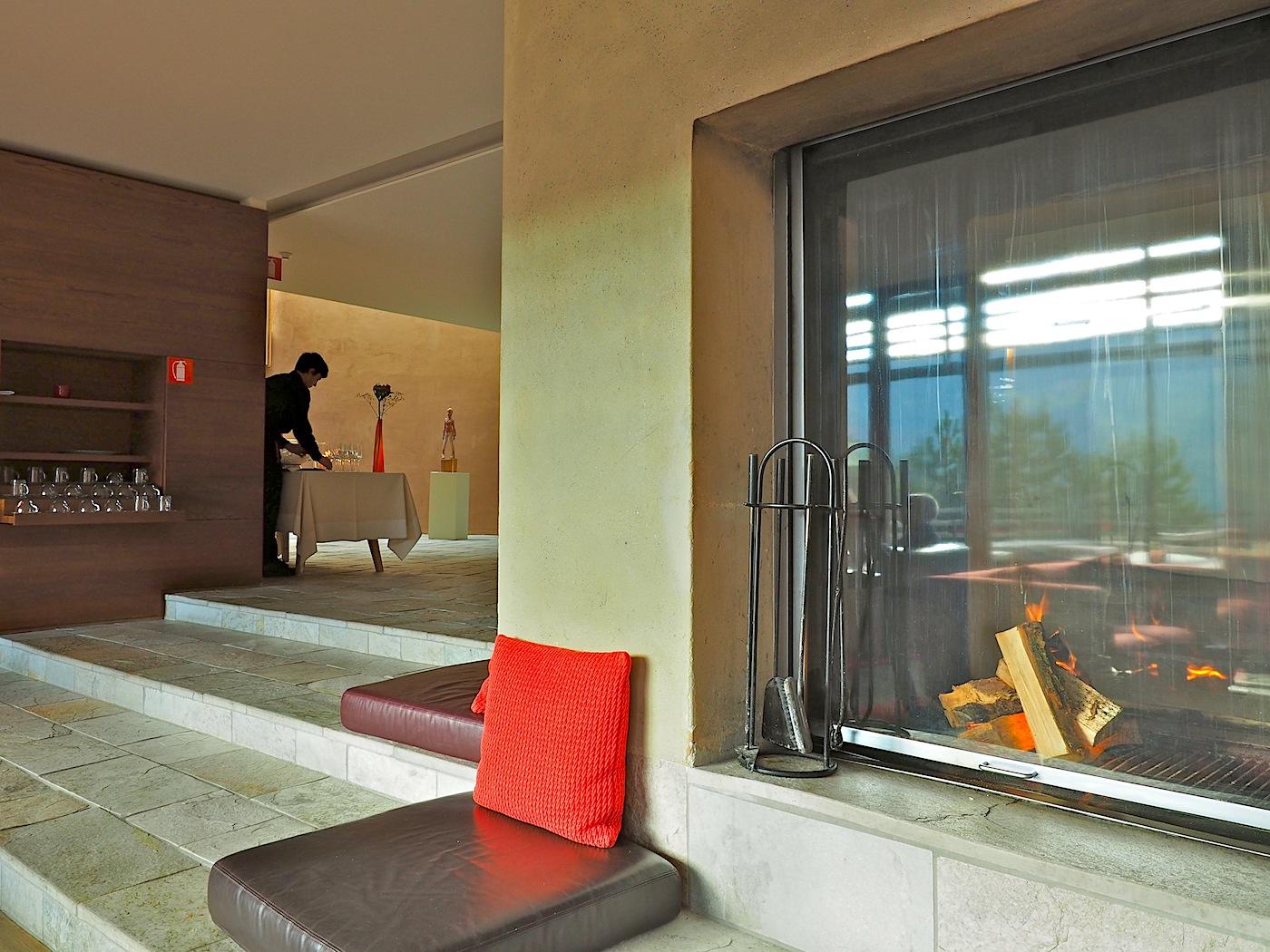 Piazza. Die zu einer Terrasse hin offene Lounge mit freistehendem Kamin bietet sich an für ein ungezwungenes Beisammensein.