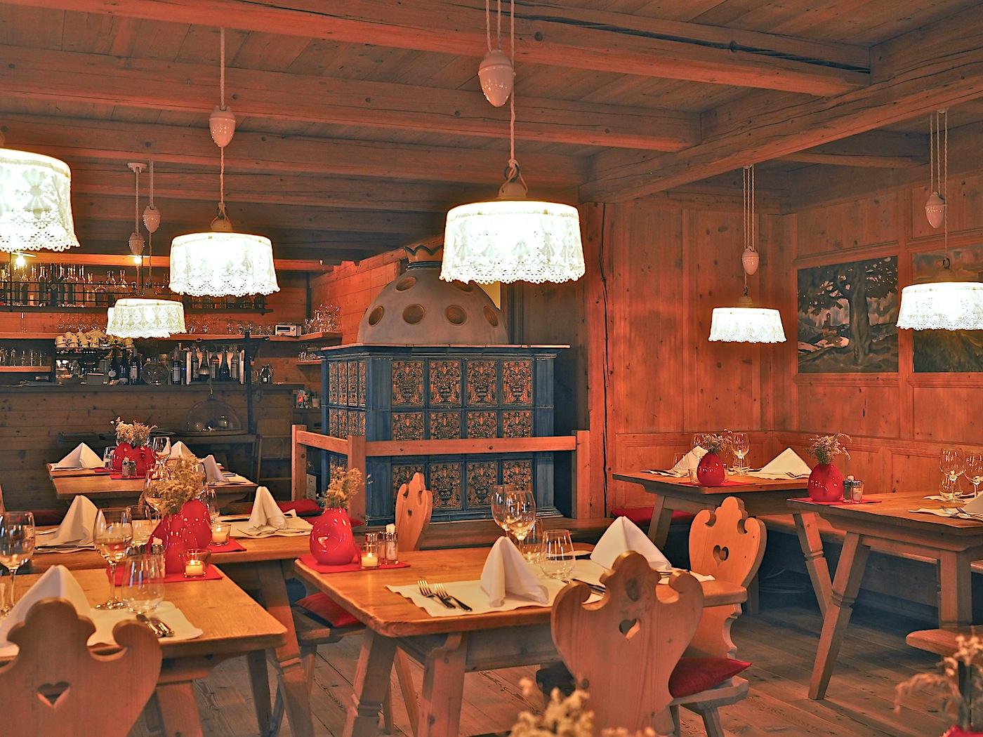 Regionale Genüsse. In der Ida-Stube, deren weitläufige Terrasse ein Bergpanorama rahmt, knüpfen Design und Kulinarik an Südtiroler Brauchtum an. Der Kachelofen wärmte schon 1912 die Gäste des alten Hotels.