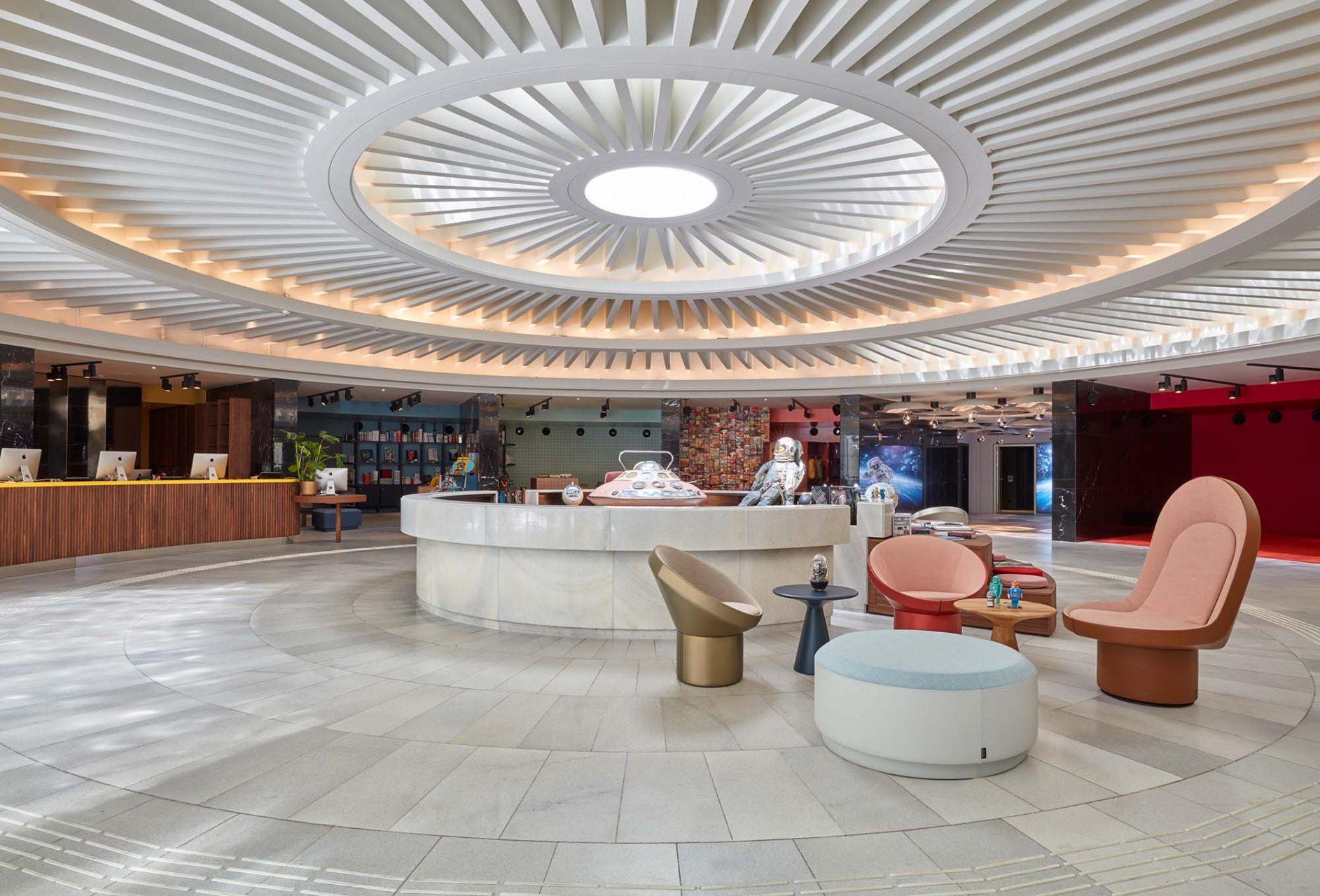 25hours Hotel The Circle. Das denkmalgeschützte kreisrunde Foyer des ehemaligen Gerling-Versicherungskonzerns bildet das spektakuläre Entrée in die Welt des 25hours Hotel The Circle. Eine überdimensionale Turbine scheint über dem Raum zu schweben.