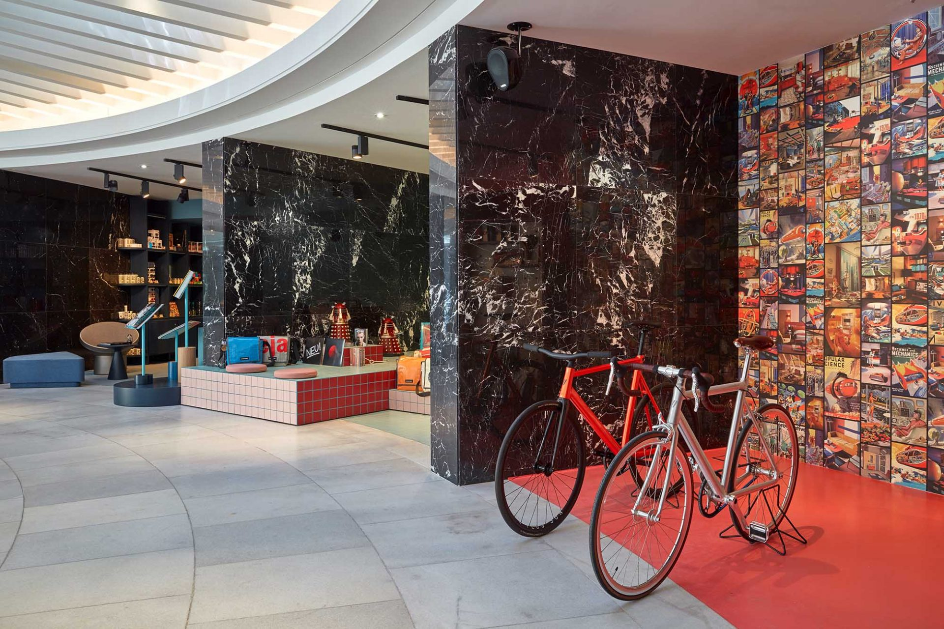 25hours Hotel The Circle. In den ehemaligen Schalternischen aus schwarzem Marmor finden sich viele Angebote für urbane Nomaden, wie die Hotel-Gruppe ihre Gäste nennt, und die Nachbarschaft, ein Buchladen mit ausgesuchtem Design-Nippes, ein Record Store mit Vinyl, ein Sound-Raum mit Polstern und ein Shop mit Rädern der Berliner Fahrradmanufaktur Schindelhauer.