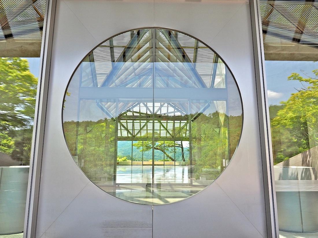 Einbezogene Natur. Ab der Eingangstür auf Gleitschienen öffnet das Gebäude immer wieder den Blick auf Bäume und Berge. Der runde Rahmen in der Tür nimmt Bezug auf Formen, die Pei aus den chinesischen Gärten seiner Jugend vertraut waren.