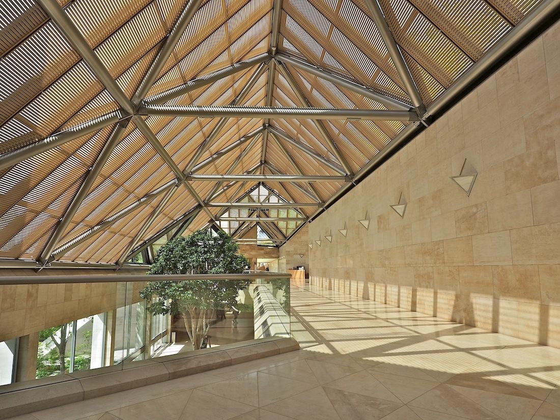 Warmes Licht. Aus dem traditionellen Baustoff Bambus hätte der Architekt die Lamellen gerne gehabt, die das Licht von oben filtern. Technische Gründe sprachen dagegen, doch in Form und Farbe haben die Jalousien aus Aluminium nun die gleiche Anmutung, ein perfektes Pendant zu dem honigfarbenen Kalkstein aus Frankreich.
