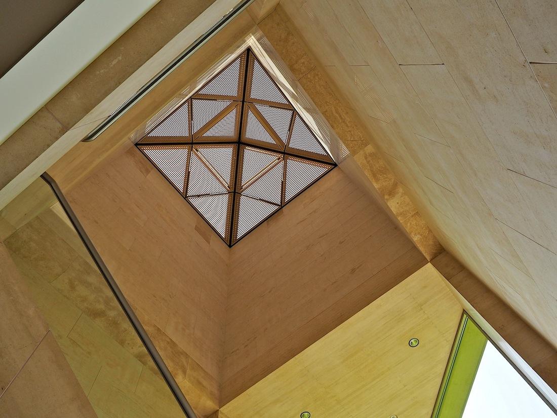 Wesensmerkmale. Im Treppenhaus zum Obergeschoss konzentrieren sich Charakteristika des Baus: geometrische Muster, bambusartige Lamellen und und der warme Ton der Sandsteinplatten.