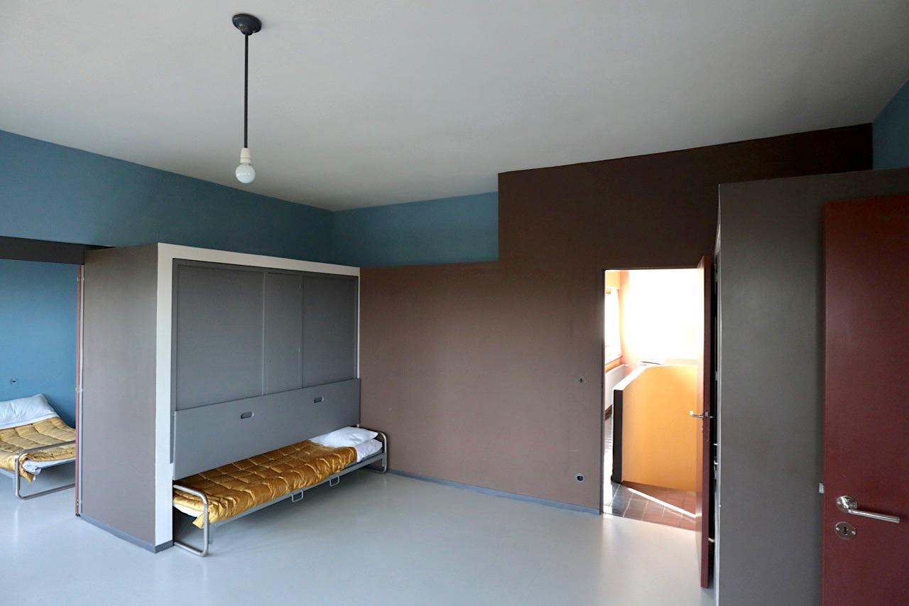 Weissenhofmuseum im Haus Le Corbusier. Für das Wohnzimmer in der rechten Doppelhaushälfte ließen sie sich von Zügen inspirieren. Das Wohnzimmer konnte man durch Schiebewände und Schiebebetten in mehrere Schlafzimmer umwandeln.