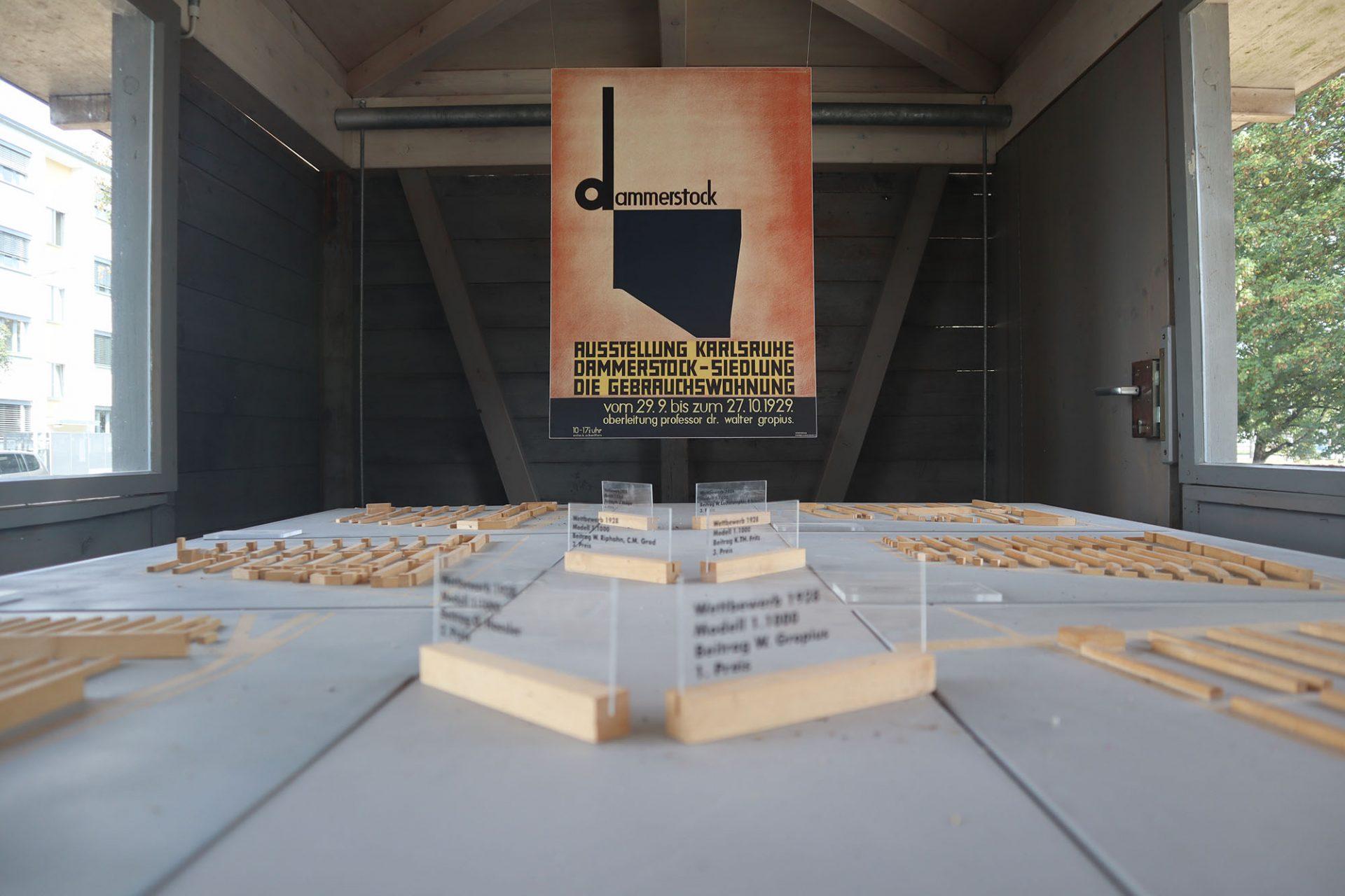 Dammerstock-Siedlung. Der Pavillonbau bildet wieder das Tor zur Anlage und informiert über die Siedlung. Das damalige Programm und die Poster gestaltete der Dadaist und Typograf Kurt Schwitters.