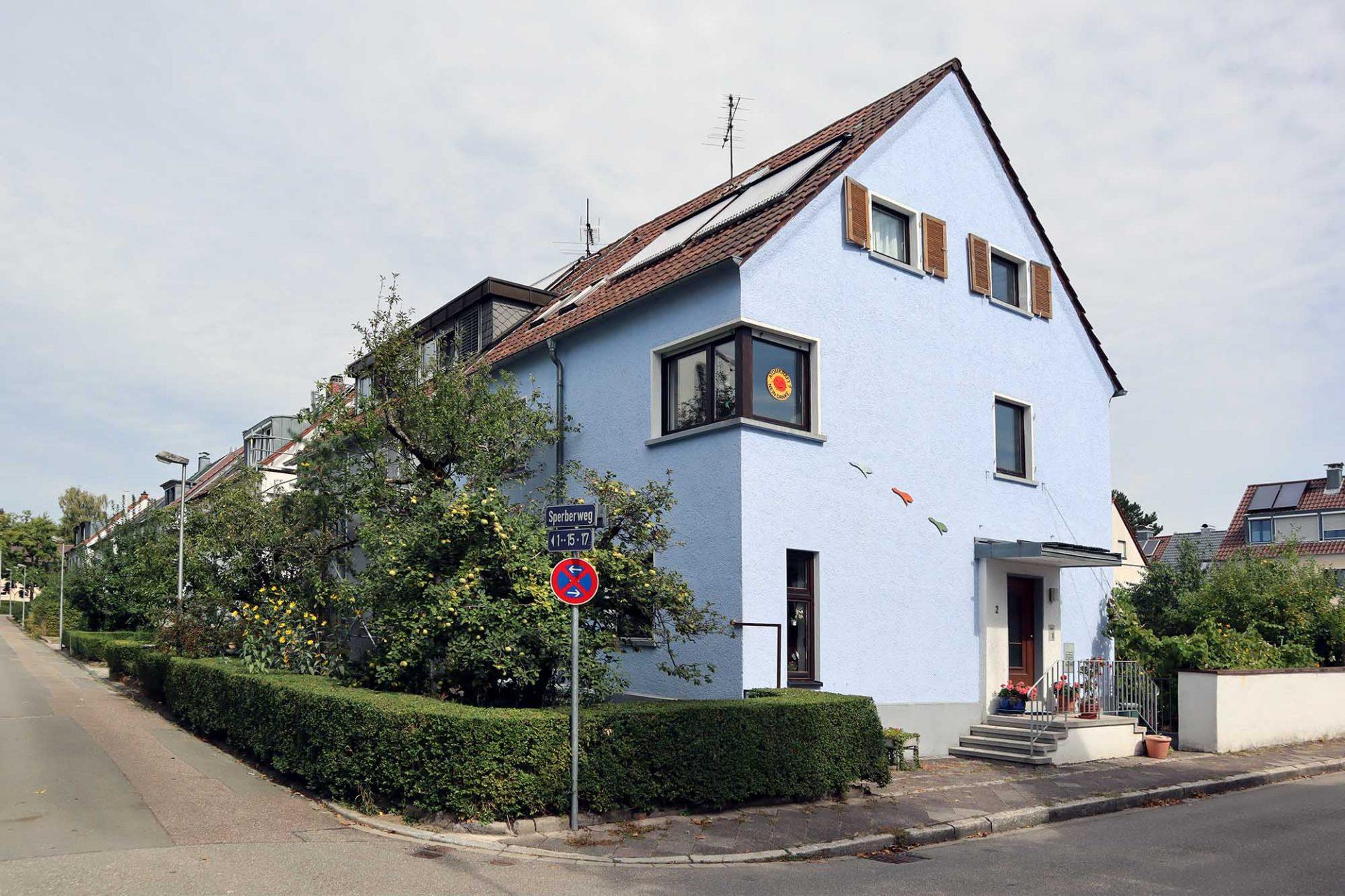 """Dammerstock-Siedlung. Der Systembruch ist auch in der Dammerstock-Siedlung abzulesen. Die Machthaber des Dritten Reichs verabscheuten die """"fremdländische Architektur"""" und errichteten im 2. Bauabschnitt ausschließlich Häuser mit """"heimischem Giebel"""" oder ersetzten die ehemaligen Flachdächer durch Schrägdächer, wie hier im Sperberweg gegenüber der 1936 errichteten St. Franziskus Kirche."""