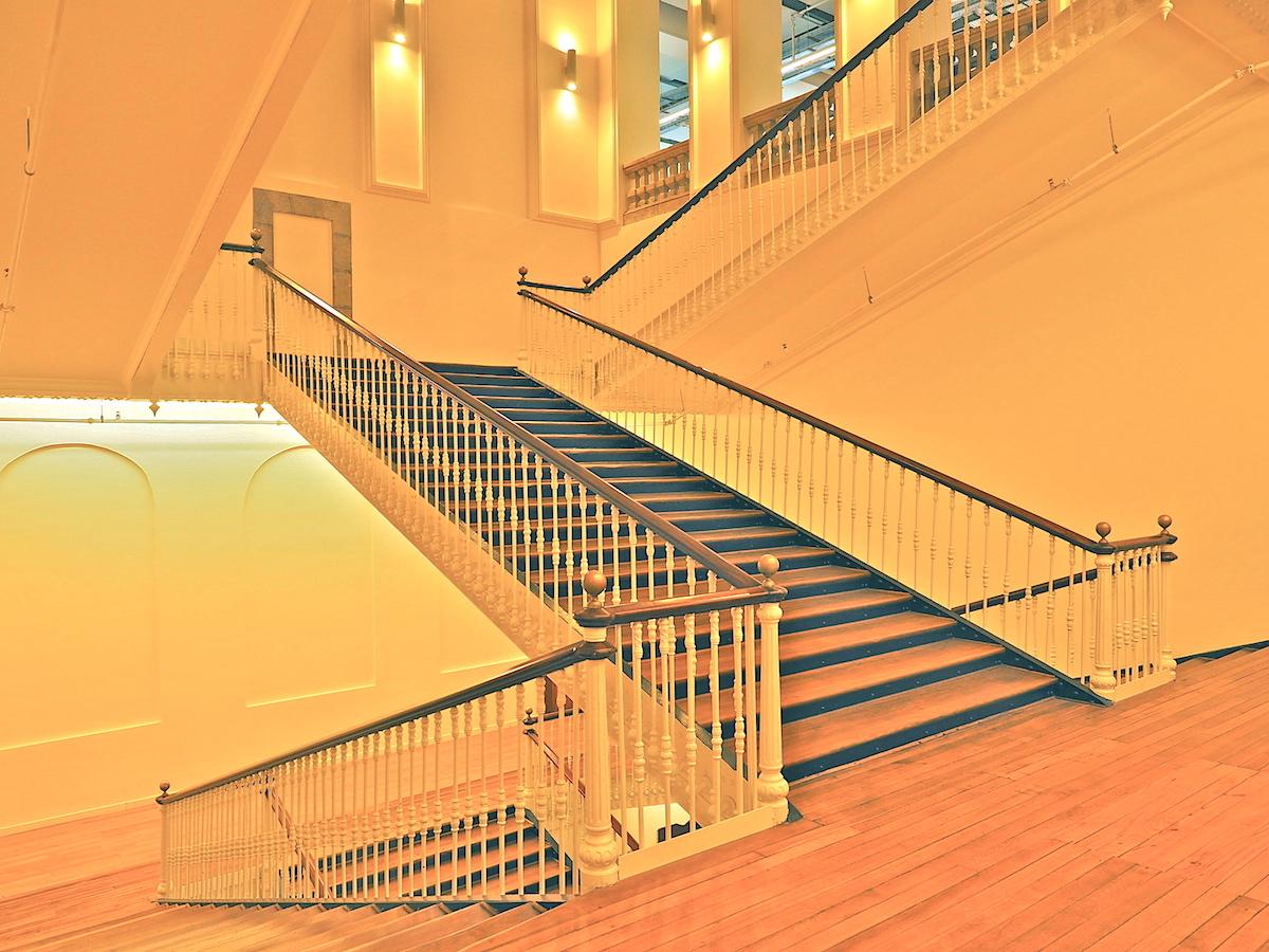 Aufgang zur Arbeit.. Das zentrale Treppenhaus erschließt die drei Geschosse, in deren Sälen früher die Tabakwaren gefertigt wurden und sich heute in Büros, Werkstätten, Ausstellungsräumen und Kinos alles um die digitale und audiovisuelle Kultur dreht.
