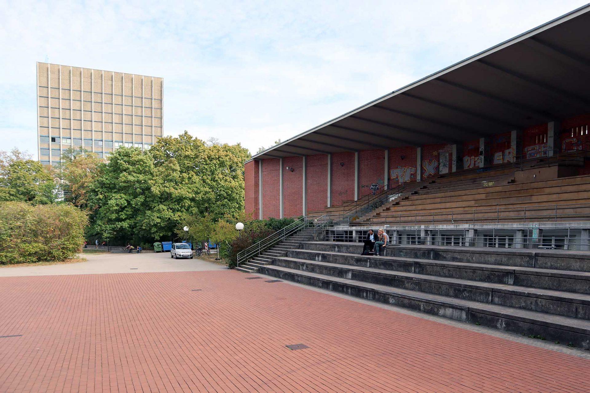 Hochschulstadion. Der Tribünenbau war ursprünglich Teil eines größeren Masterplans, der aber nie vollständig ausgeführt wurde. Heute steht er inmitten von Universitätsbauten späterer Jahre.