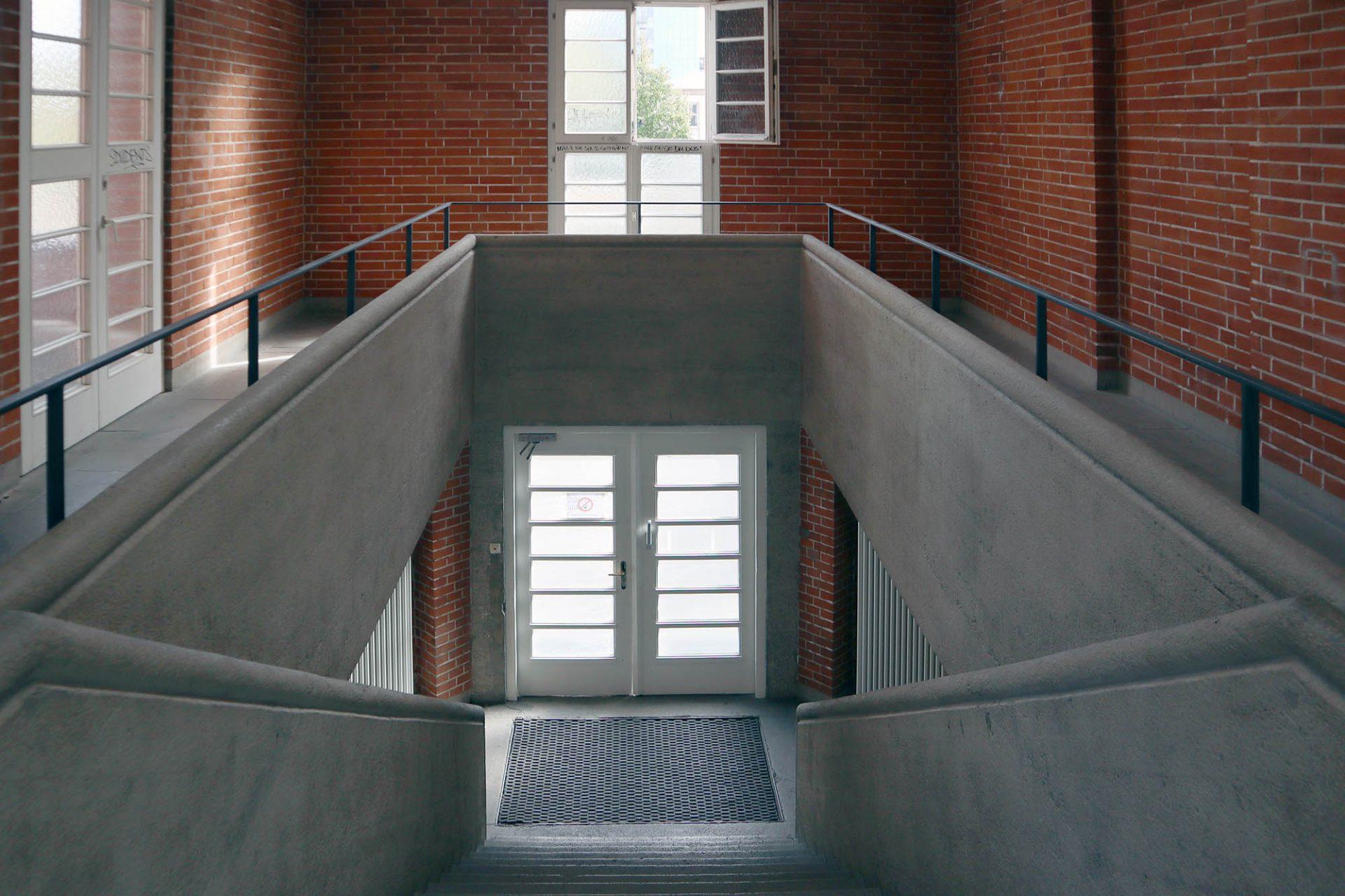 Hochschulstadion. Beton und Ziegelstein kontrastieren auch in den beiden Treppenräumen und im imposanten Gymnastiksaal unter der Tribüne.