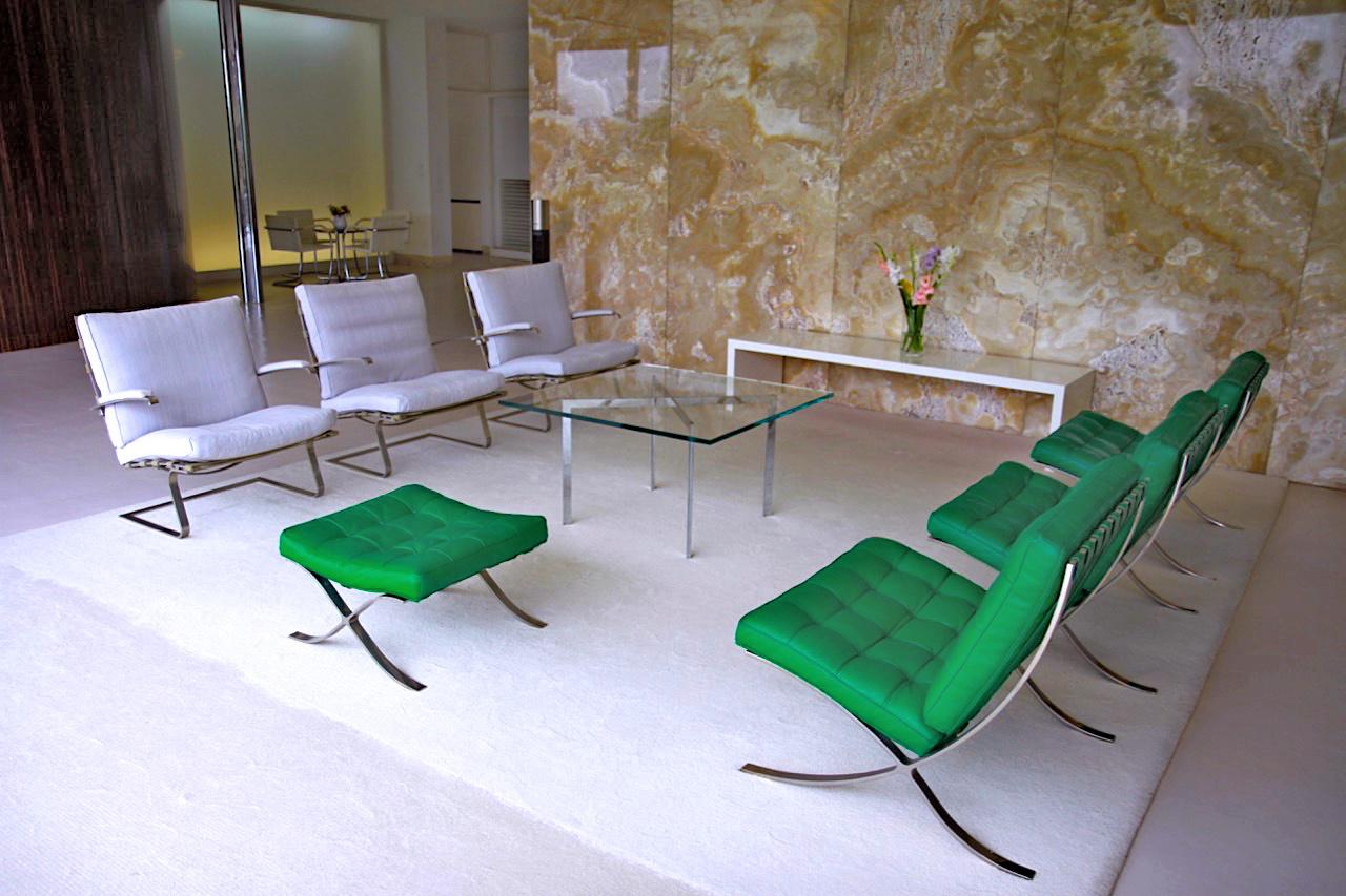 Villa Tugendhat. Sitzgruppe mit drei Barcelona-Sessel und einem Barcelona-Hocker mit smaragdgrünem Lederpolster. Die drei Tugendhat-Sesseln gegenüber sind aus Rodierstoff.
