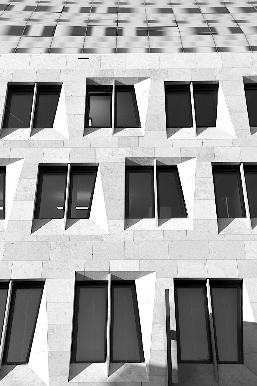 Dorotheen Quartier. Die Kalksteinfassade mit Dachgeschoss, das teils so hoch ist wie die darunter liegenden Geschosse.