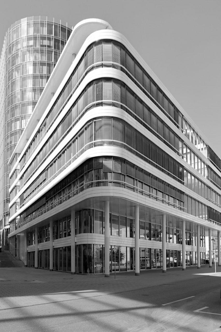 Landesbank Baden-Württemberg. 18-geschossiges Hochhaus mit scharfer Kante auf der einen Seite, der Sockelbau mit horizontal umlaufenden Fassadenbändern aus weiß glasierten Baukeramikplatten auf der anderen Seite. Das Gebäude steht unweit der Stadtbibliothek.