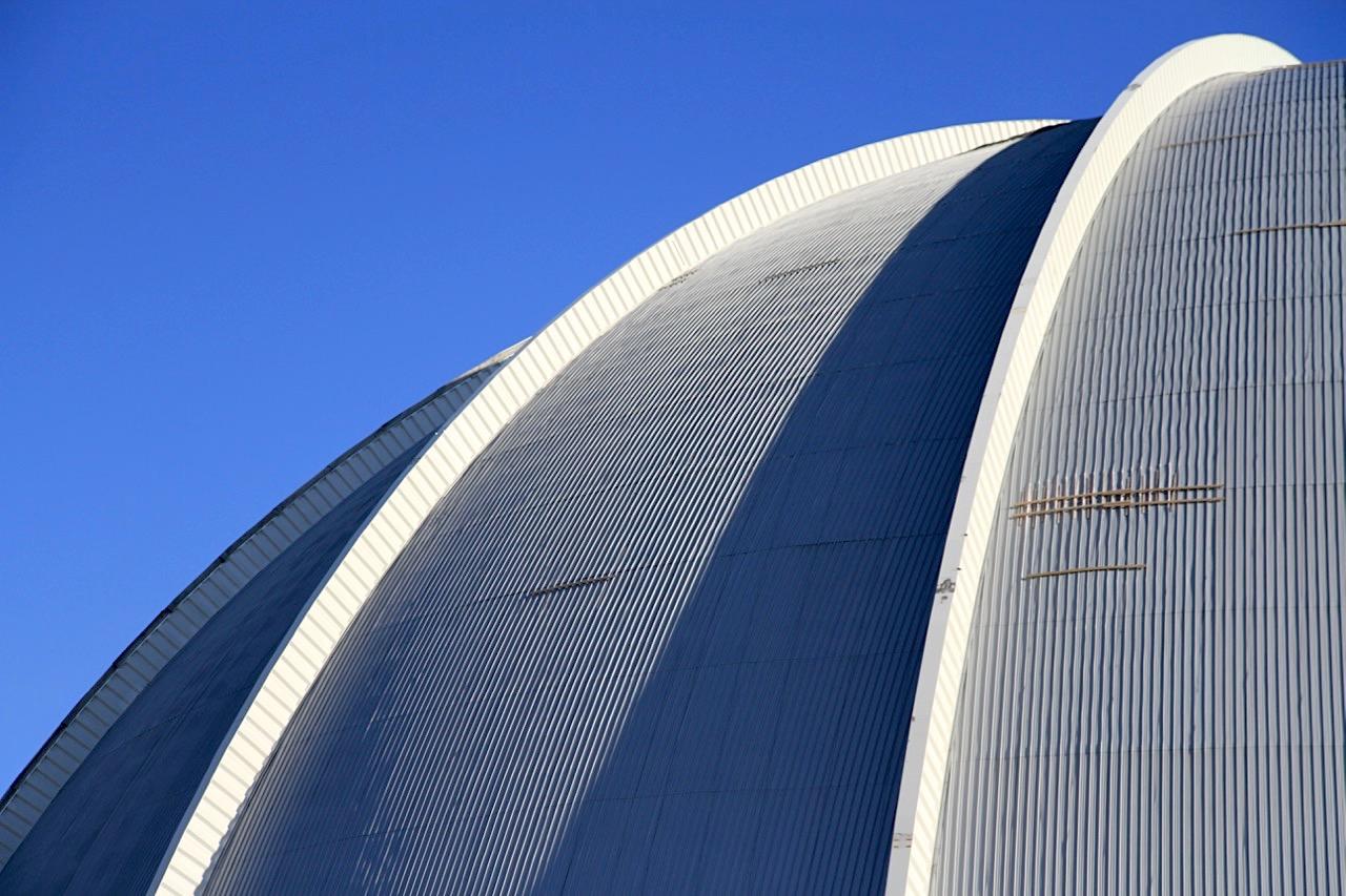 """Bogenfest. 1999 wurde nach zwei Dutzend Entwurfsrunden der Masterplan für den Luftschiffhallenbau festgeschrieben. Im gleichen Jahr begannen die Bauarbeiten, im Herbst war der erste von fünf Bögen aufgebaut. Das als """"Bogenfest"""" bezeichnete Richtfest feierten 25.000 Gäste."""