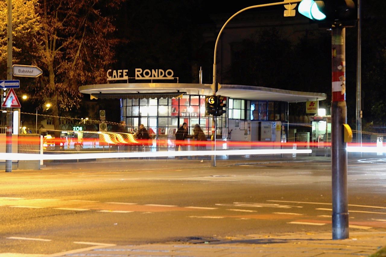Café Rondo. Ein freistehender Mauerwerksbau mit Flachdach und großflächigen Eisen-Glas-Fenstern, die den Krümmungen des Grundrisses in Form dreier, ineinander verschnittener Kreise folgen.