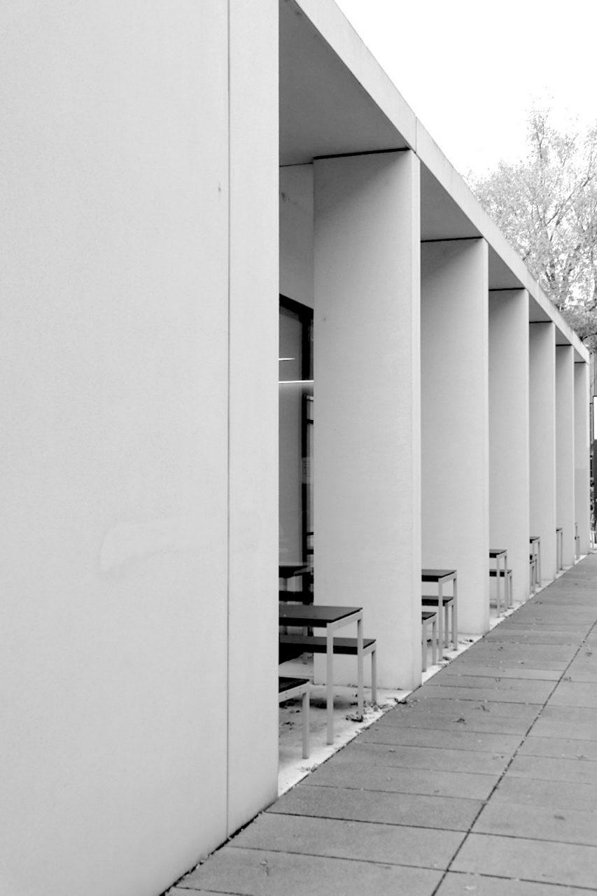 Cafeteria Markusgelände. Entwurf: Gerhard Grellmann, Rainer Kriebel, Christian Teichmann, GKT Architekten. Fertigstellung: 2013. Das einstöckige, komplett verglaste Gebäude wurde aus weißen, gesäuerten Fassadenelementen erstellt. Das Stützraster der weißen Betonelemente greift das historische Thema der Arkade auf.
