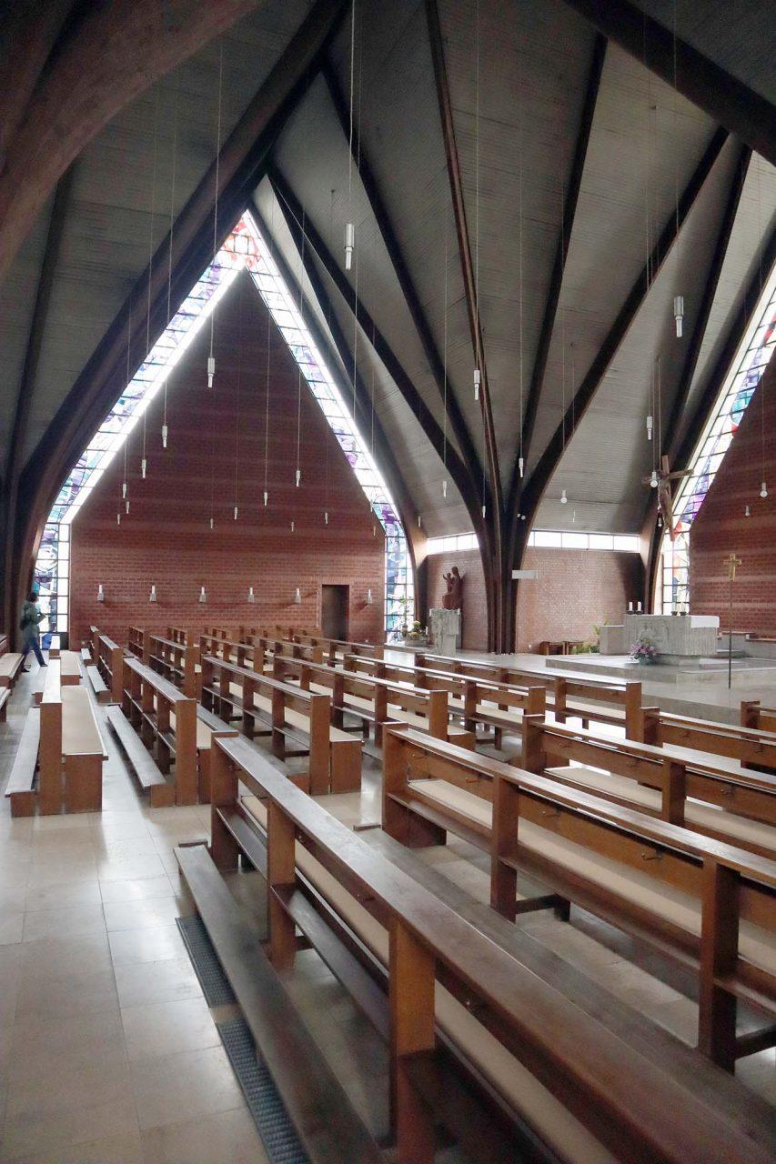 St. Josef. Das Innere ähnelt einem Zelt, bedingt durch die hochaufragende und dachtragende Holzkonstruktion. Hinzu kommen die Materialien Glas, Beton und Stein, die in diesem Bau vielfach ineinanderzufließen scheinen.