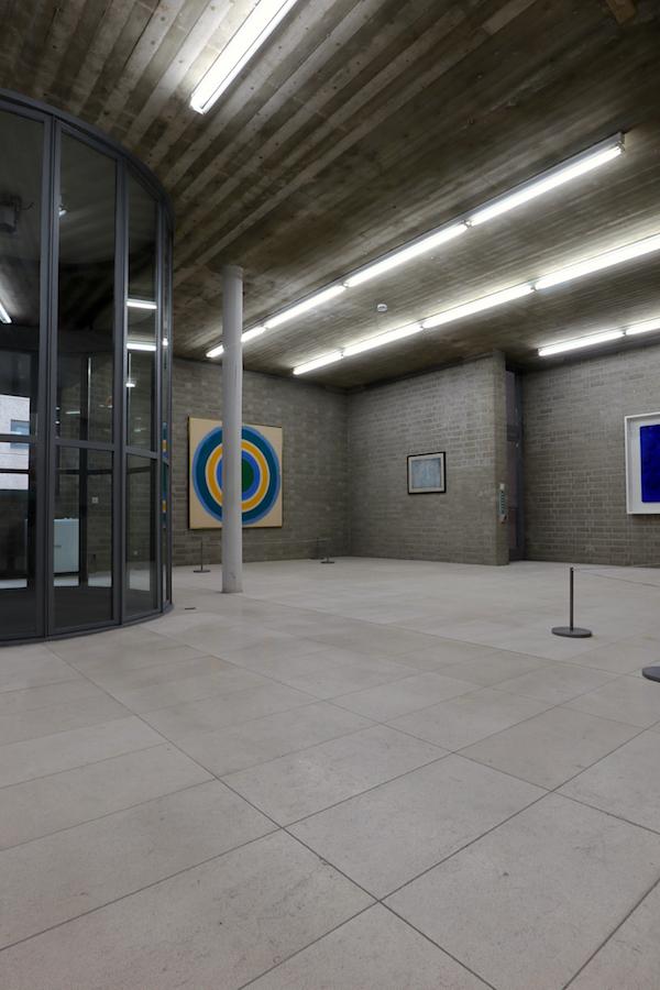 """Schmela Haus. Das Gruppenbild wie links das Bild """"Bloom"""" von Kenneth Noland (1960) und Relief éponge von Yves Klein (1960, rechts) sind in der Etage über dem Eingang zu sehen."""