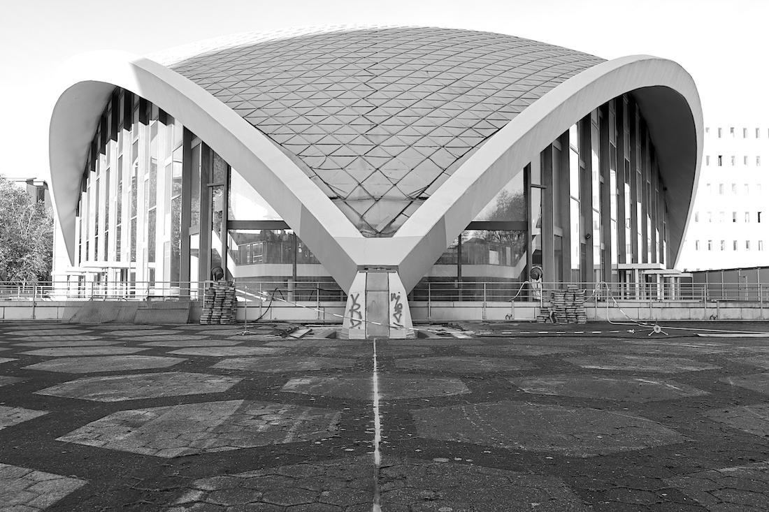 Opernhaus Dortmund. Die dreipunktgelagerte Schale scheint über dem Sockelbau zu schweben. Dem großflächig verglasten Gebäude ist ein weitläufiger Platz vorgelagert.