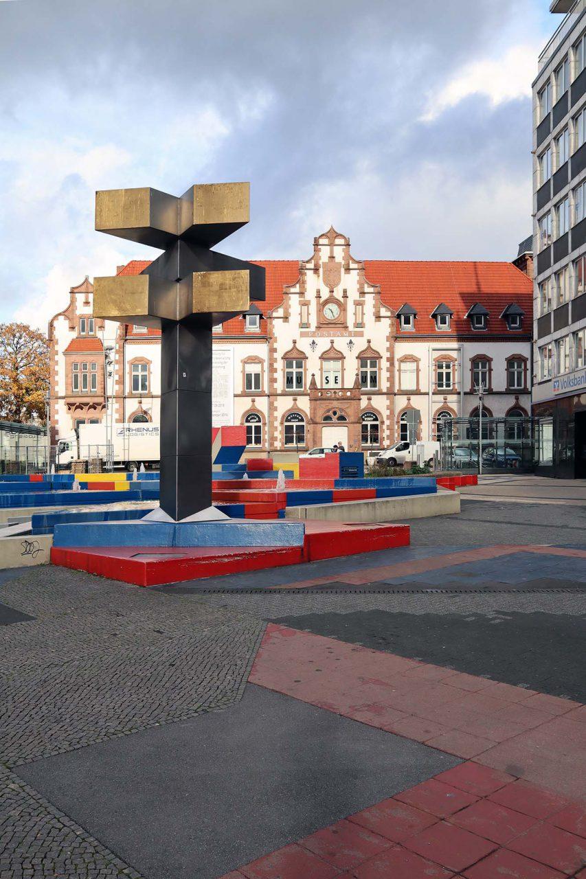 """Synagogenplatz. Die Installation """"Stadtikonographie mit Stadtzeichen, Sitzlandschaft und Brunnenanlage"""" ist eines der wenigen erhalten Werke des Künstlers Herbert Hajek."""
