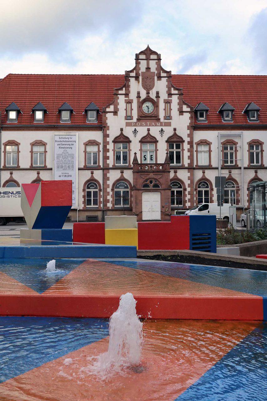 """Synagogenplatz. Mit seinen raumgreifenden, farbigen """"Stadtikonographien"""" wurde er besonders seit den 1970er-Jahren zu einem bedeutenden Wegbereiter moderner Kunst im öffentlichen Raum."""