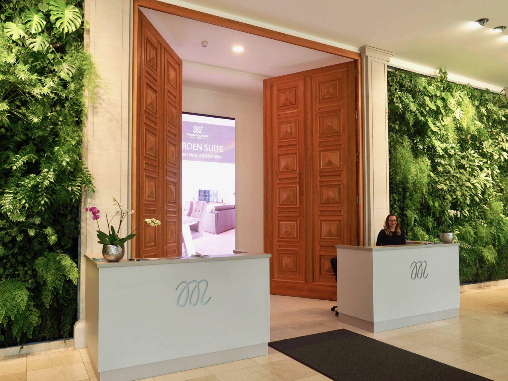 Offener Empfang. Die halb geöffneten Flügeltüren in der Lobby sind der Zugang zu den Apartments. Das Display dahinter fächert das Angebot des Aparthotels auf.