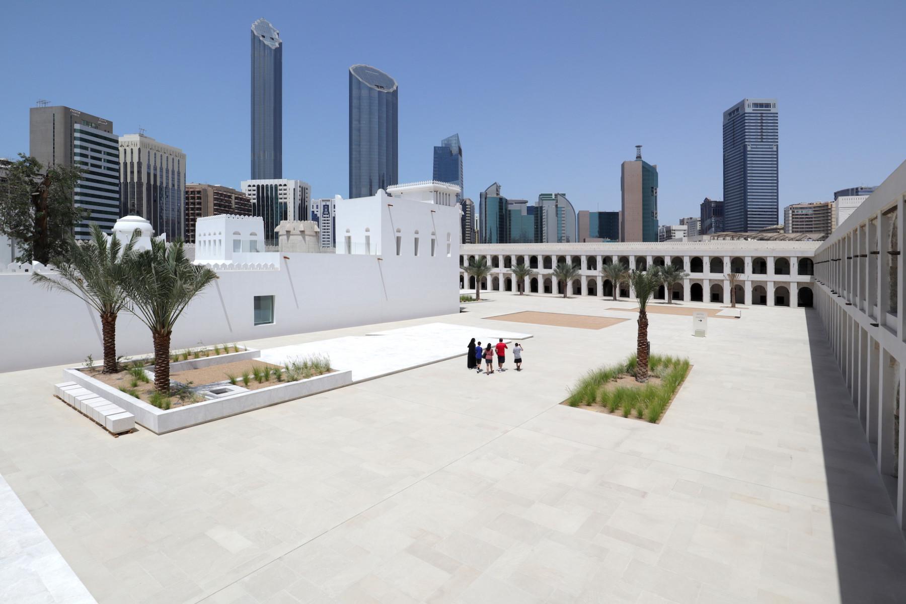 """Qasr Al Hosn. ... einem äußeren Palast (""""Qasr""""). Im Hintergrund stehen links die zwei von Foster+Partners entworfenen Wolkenkratzer des World Trade Center Abu Dhabi."""