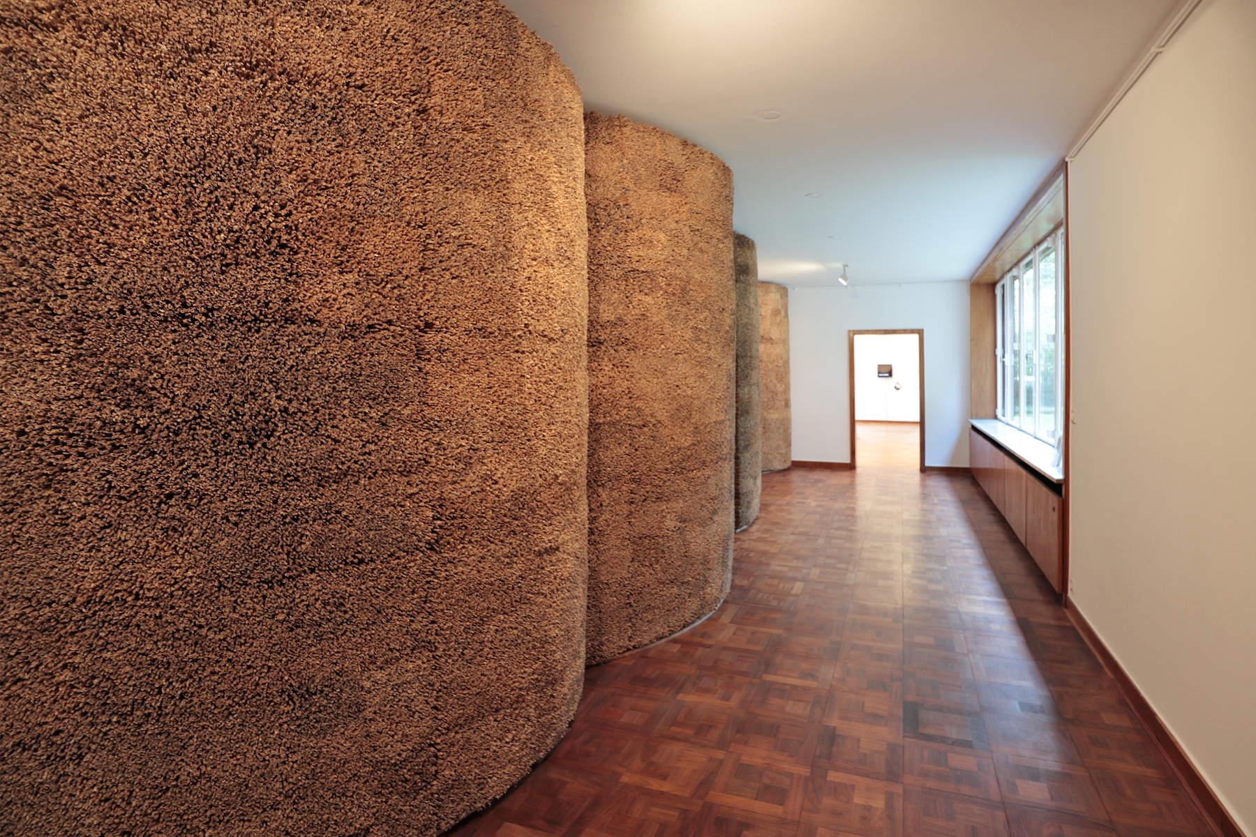 """Haus Lange. Die zweigeschossigen Häuser konstruierte er aus Mauerwerk und Stahlträgern. Die Fassaden wurden mit dunkelrotem Backstein verkleidet. Links die Installation von Olaf Holzapfel in der Sonderausstellung """"Anders wohnen""""."""