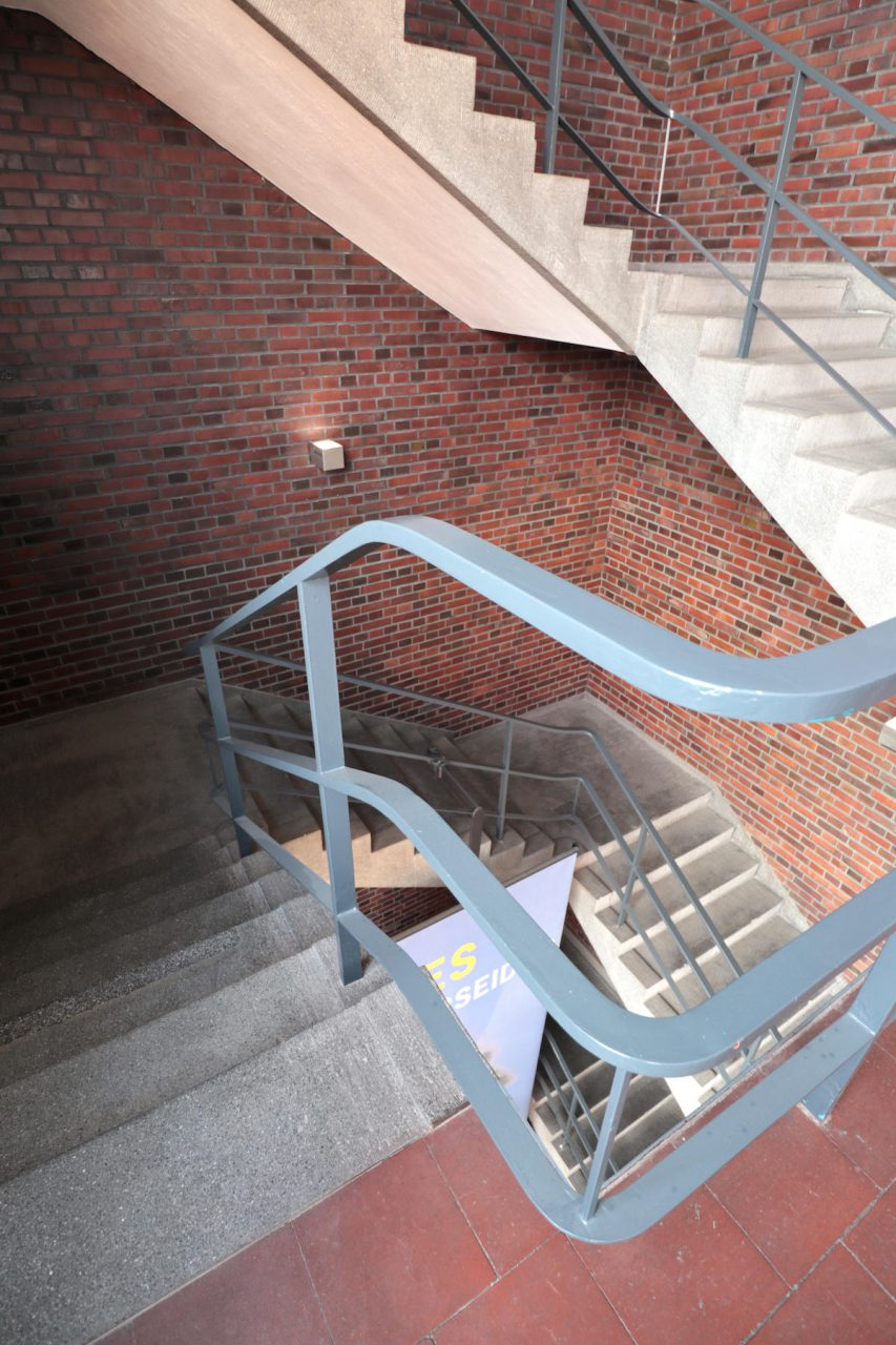 Mies van der Rohe Business Park. Außen weiß und schlicht, innen schwungvoll und mit Backstein: das Treppenhaus des HE-Baus (HE = Herren-Futterstoffe).