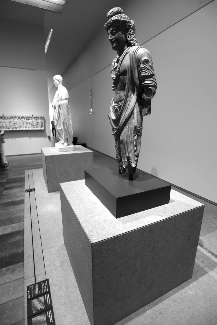 Louvre Abu Dhabi. Die Statuen aus Rom und Gandhara stammen aus dem 1. Jahrhundert v. Chr. und stehen für die Dualität des Museums und seiner Architektur.