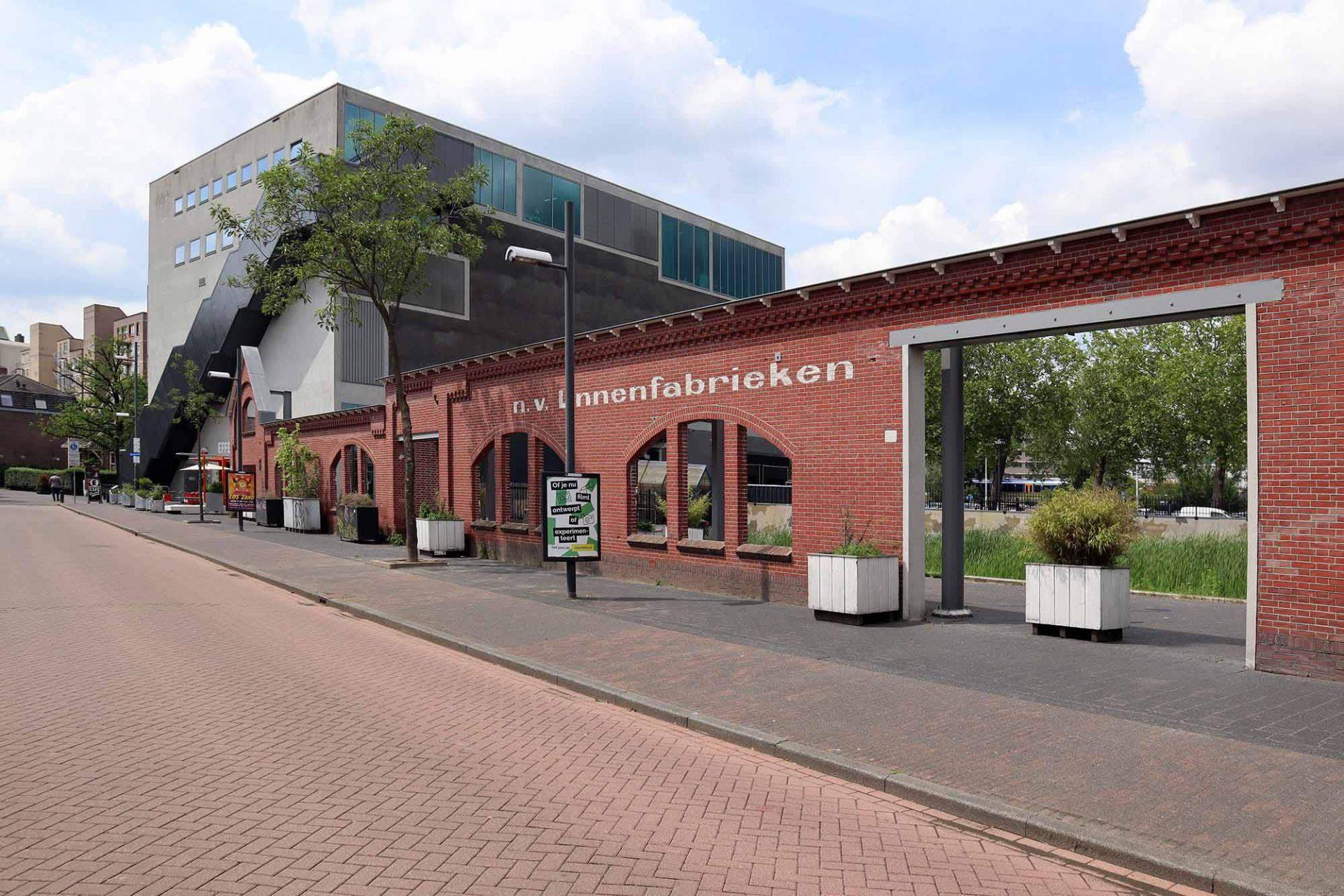 """De Effenaar. Der alte Musikclub """"Effenaar"""" prägte mit Rock- und Popkonzerten ganze Generationen von Jugendlichen in Eindhoven. Er befand sich in einer ehemaligen Leinenfabrik von der nur noch die Mauern erhalten sind. Die Veranstaltungen finden seit 2005 in einem Neubau nach Plänen von MVRDV auf dem benachbarten Grundstück statt."""