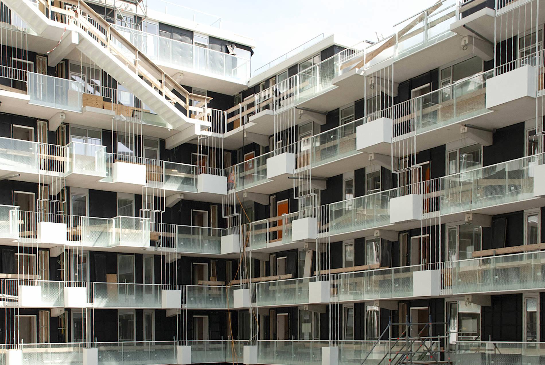 Fenix I. Der obere Baukörper umrundet einen begrünbaren Innenhof. Über Laubengänge werden die Apartments erschlossen.