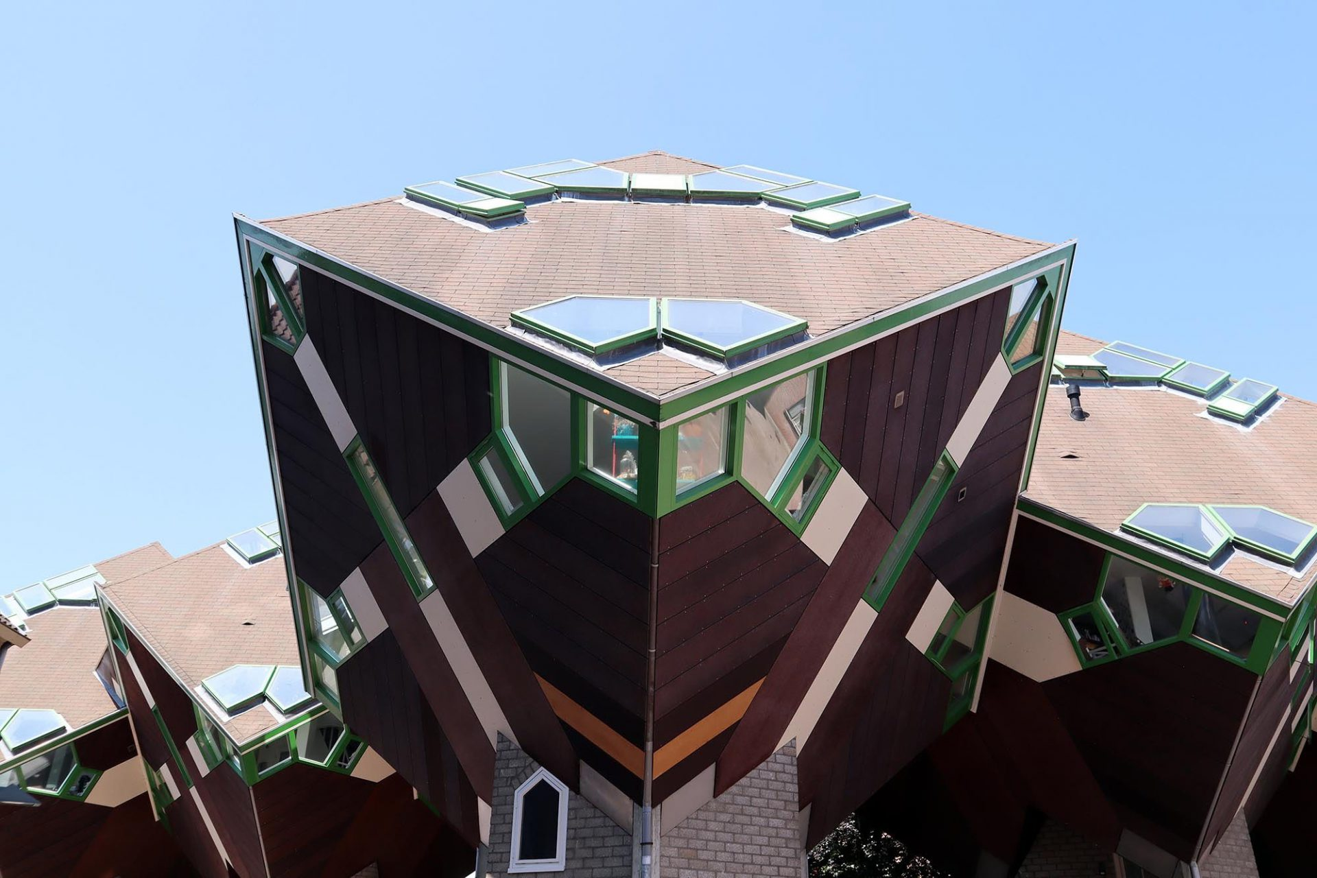 Kubushäuser. Auf den Kopf gestellte Wohnwürfel mit äußerst schrägen Wänden, frei eingezogenen Bodenbereichen und abgelöst vom Boden.