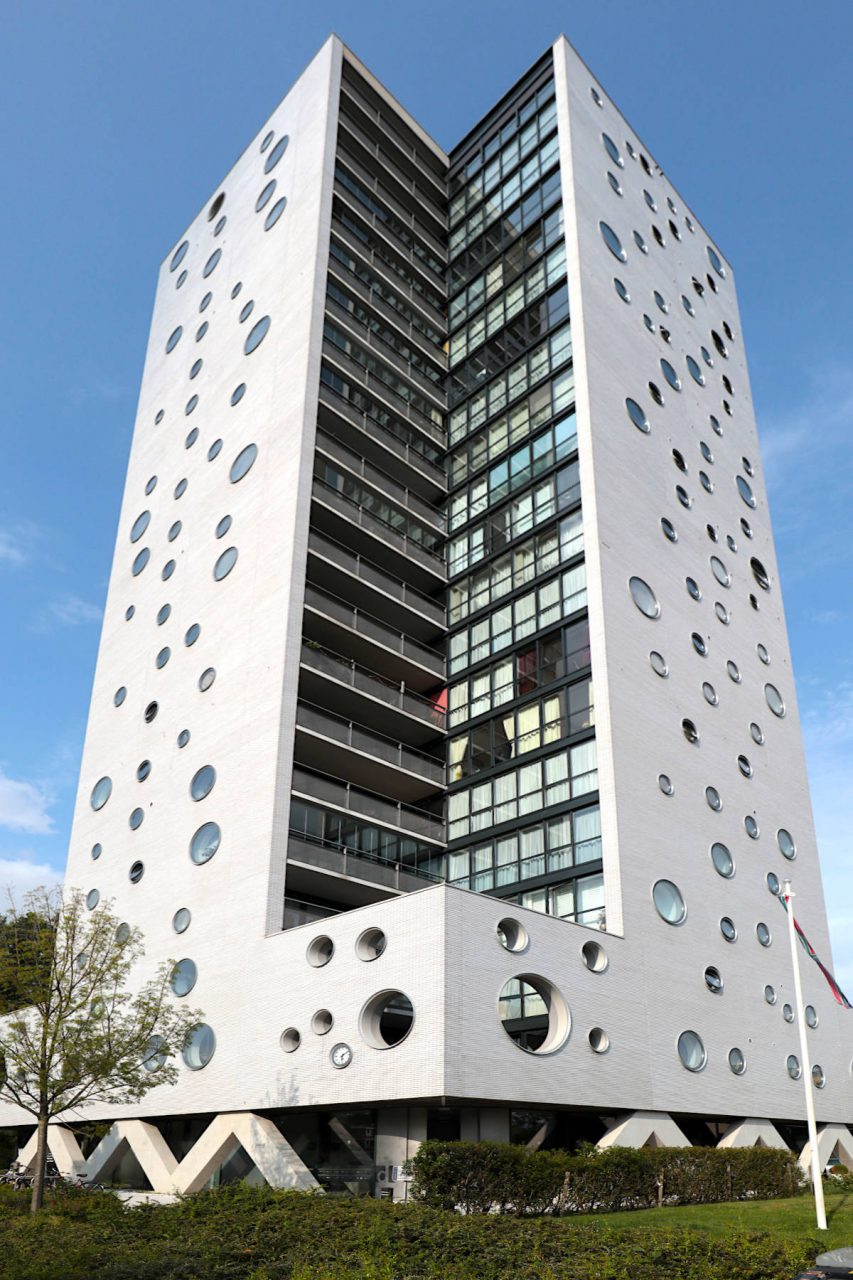 """De Rokade. Arons en Gelauff Architecten, 2008. Der Wohnturm ist 63 Meter hoch und gehört mit seinen 21 Etagen zu den höchsten Gebäuden der Stadt. """"De Intense Stad"""" war ein Baumanifest und Plan der Stadt zur Verdichtung und Anbindung der Stadtteile an das Zentrum. """"Die Rochade"""" ist eines der ersten sichtbaren Ergebnisse dieses Vorhabens. Die Landschaftsarchitektur stammt von Kraaivanger Urbis."""