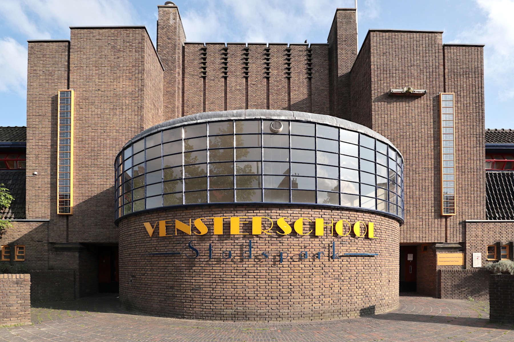 Vensterschool. In der Parkstraße, S.J. Bouma. Fertigstellung: 1927. Die Vorder- und Rückseite unterscheiden sich stark. Die Amsterdamer Schule zeigt sich vorne mit einer geschlossenen, gegliederten Front und ...