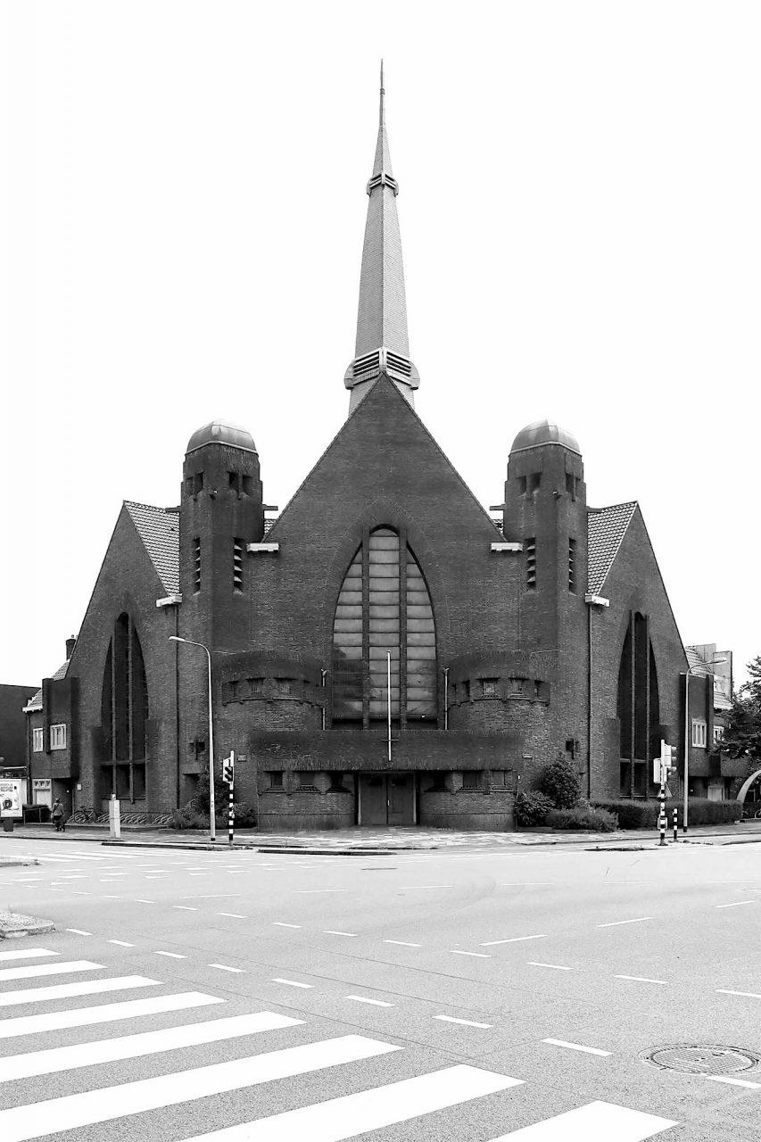 """Oosterkerk. Jan Kuiler (1883–1952) und Lucas Drewes (1870–1969) war ein Architektenduo aus Groningen, wo sie für den Bau mehrerer Gebäude verantwortlich waren – darunter auch die expressionistische Kirche, das ein """"Rijksmonument"""" ist, ein nationales Denkmal."""